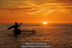 Boys paddling their pirogue into the sunset, Baramahamay Estuary