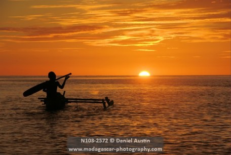 Boys paddling their pirogue into the sunset, Baramahamay Estuary